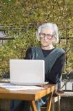 90 Jahre alte Frau, die einen Videoanruf auf einem Notizbuch haben Lizenzfreies Stockfoto