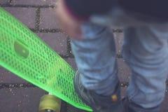 7 Jahre alte Junge in den Jeans, die auf Skateboard, Herbst, selektiver Fokus stehen Lizenzfreies Stockbild