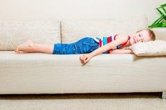 6 Jahre alte Junge, die auf der Couch liegen Lizenzfreies Stockbild