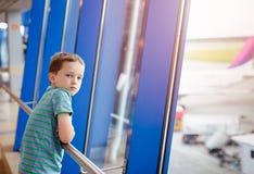 7 Jahre alte Junge, die auf sein Flugzeug am Flughafen warten Stockfotos