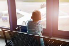 7 Jahre alte Junge, die auf sein Flugzeug am Flughafen warten Lizenzfreie Stockfotos