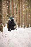 8 Jahre alte Junge, die ein Schneeschloss errichten und mit Schneebällen im Wald spielen Lizenzfreies Stockfoto