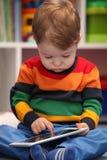 2 Jahre alte Junge, die einen digitalen Tablet-Computer verwenden Lizenzfreies Stockbild