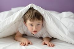7 Jahre alte Junge, die im Bett unter einer weißen Decke oder einer Bettdecke sich verstecken Lizenzfreie Stockbilder