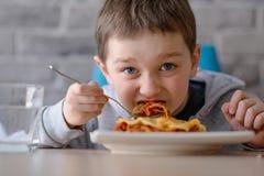7 Jahre alte Junge, die Lasagne in Esszimmer essen Stockfotografie