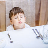 3 Jahre alte Junge an einem leeren Tisch Stockfotografie