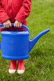4 Jahre alte Junge in einer roten Jacke und in Gummistiefeln wird einen Baum und von einer netten großen blauen Gießkanne wässern Stockfoto