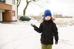 6 Jahre alte Junge spielt mit Schnee im Hinterhof Lizenzfreies Stockbild