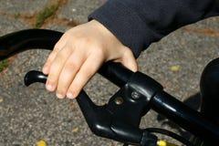 4 Jahre alte Jungenhand auf schwarzer Fahrradgriffbremse Lizenzfreies Stockfoto
