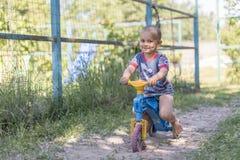 2 Jahre alte Jungenspiel mit Fahrrad, Balancenfahrrad Junge 2 Jahre, die Fahrrad durch das Dorf fahren Lizenzfreies Stockbild