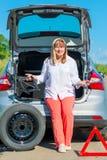 50 Jahre alte lächelnde Frau nahe dem Auto Stockfoto