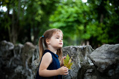 3 Jahre alte Mädchen in einem Zoo mit einem Blatt in einer Hand Stockfotografie