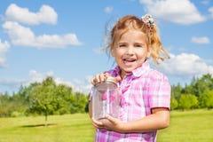 6 Jahre alte Mädchen mit Schmetterlingsglas Stockbilder