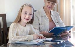 10 Jahre alte Mädchen und ihr Lehrer Studie des kleinen Mädchens während ihrer privaten Lektion Tutor- und pädagogisches Konzept Stockfotografie