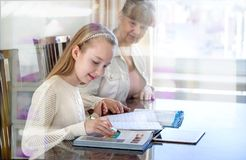 10 Jahre alte Mädchen und ihr Lehrer Studie des kleinen Mädchens während ihrer privaten Lektion Tutor- und pädagogisches Konzept Lizenzfreies Stockbild