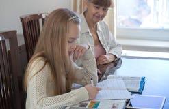 10 Jahre alte Mädchen und ihr Lehrer Studie des kleinen Mädchens während ihrer privaten Lektion Tutor- und pädagogisches Konzept Lizenzfreie Stockbilder