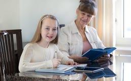 10 Jahre alte Mädchen und ihr Lehrer Studie des kleinen Mädchens während ihrer privaten Lektion Tutor- und pädagogisches Konzept Lizenzfreie Stockfotos