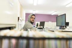 40 Jahre alte Mann, die Computer schauen und mit dem Sweatshirt arbeiten Stockfotografie