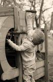 2 Jahre alte neugierige Baby, die mit altem landwirtschaftlichem Mach handhaben Lizenzfreies Stockbild