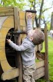 2 Jahre alte neugierige Baby, die mit altem landwirtschaftlichem Mach handhaben Stockbilder