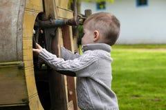 2 Jahre alte neugierige Baby, die mit altem landwirtschaftlichem Mach handhaben Lizenzfreie Stockfotos