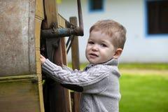 2 Jahre alte neugierige Baby, die mit altem landwirtschaftlichem Mach handhaben Stockfoto