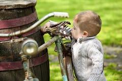2 Jahre alte neugierige Baby, die um das alte Fahrrad gehen Stockfoto