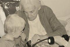 90 Jahre alte Urgroßmutter verbringt Zeit mit ihren zwei Jahren alten Großenkel Stockfoto