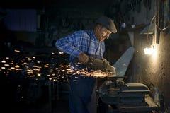 90 Jahre alter Schmiedereibende Axt in seiner Werkstatt Lizenzfreie Stockfotos