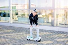 10 Jahre altes Mädchenreiten auf selbstabgleichendem elektrischem Skateboard Stockfoto