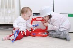 4 Jahre Bruder und 10 Monate Schwesterspiel behandeln zu Hause Lizenzfreie Stockfotos