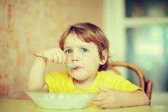 2 Jahre des Kindes selbst isst von der Platte Lizenzfreie Stockfotografie