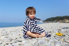 2 Jahre Junge in der gestreiften Decke, die auf den Kieseln sitzt, setzen auf den Strand Lizenzfreies Stockfoto