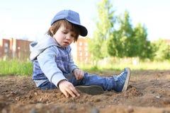 2 Jahre Junge, die mit Sand spielen Stockfotografie