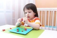 3 Jahre Junge mit dem langen Haar, das Apfelbaum von playdough modelliert Lizenzfreie Stockbilder