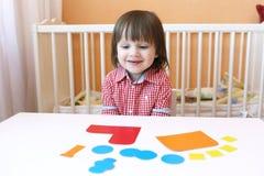 2 Jahre Kind machten Puffer von den Papierdetails Stockfotografie