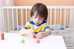2 Jahre Kind stellten Zahnstocherbeine durch playdough Spinnen her Lizenzfreie Stockfotos