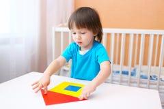 2 Jahre kleine Junge, die Haus aus Papierdetails konstruieren Lizenzfreie Stockfotografie