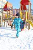5 Jahre kleine Junge im warmen Gesamten läuft draußen in Winter Stockfotografie