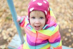 1 Jahre kleine Mädchen im Herbst draußen auf Schwingen Stockfoto