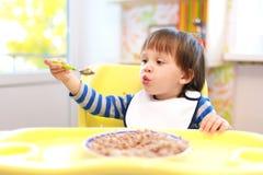 2 Jahre Kleinkind, die Buchweizengrützen essen Stockfotos