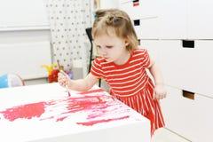 2 Jahre reizende Malerei des kleinen Mädchens Stockfotografie