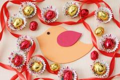 Jahreszeitdekoration: Ostern-Schokoladeneirahmen mit handgemachtem Vogel auf hölzernem Hintergrund Lizenzfreies Stockfoto