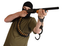 Jail break  robber in black mask with shotgun removing handcuffs Royalty Free Stock Image