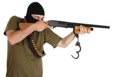 Jail break  robber in black mask with shotgun removing handcuffs Royalty Free Stock Images