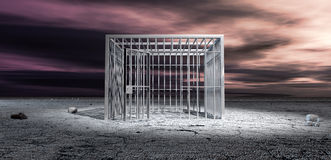 Jail Cell Unlocked In Barren Landscape. A cubic shaped metal unlocked jail cell in the middle of a barren landscape under an ominous purple sky Stock Photos