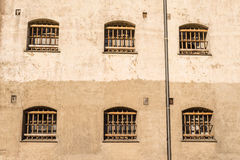 Jail wall with windows with bars Royalty Free Stock Image