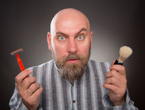 Jailbird. Astonished jailbird posing with razor and brush in his hands. Bold bearded man is very surprised isolated on dark grey Royalty Free Stock Image