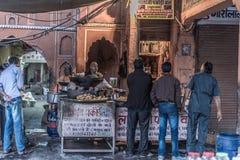 Jaipur, Índia - 5 de fevereiro de 2017: vendedor e povos de alimento em uma rua suja em Jaipur, Rajasthan, destino famoso do curs imagens de stock royalty free