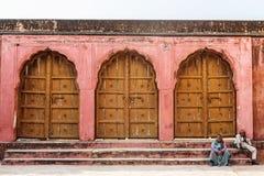 JAIPUR, ÍNDIA - 12 DE JANEIRO DE 2018: Um par indiano senta-se nas etapas perto do forte velho das portas grandes Amer Fort Fotos de Stock